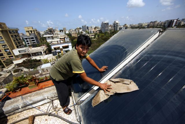 Housekeeper cleaning solar thermal panels in India