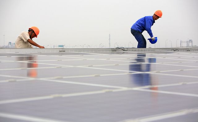 Installing solar panels on the Hongqiao Passenger Rail Terminal in Shanghai, China. Photo by Jiri Rezac/The Climate Group
