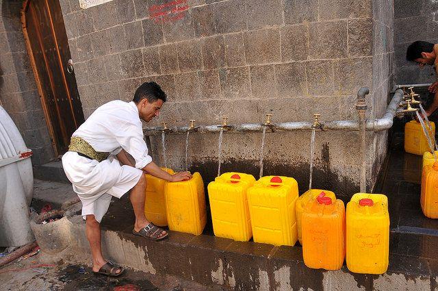 A man fills water bottles in Sanaía, Yemen Photo by Foad Al Harazi / World Bank
