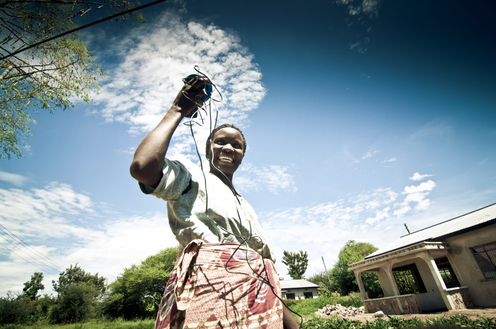 <p>Tanzanian woman holds up a pay-as-you-go solar device. Flickr/Angaza</p>
