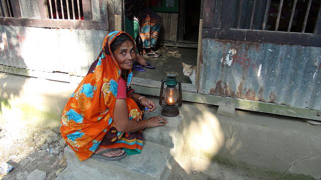 <p>Woman in Bangladesh uses a kerosene lamp. Photo by Helena Wright/Flickr</p>