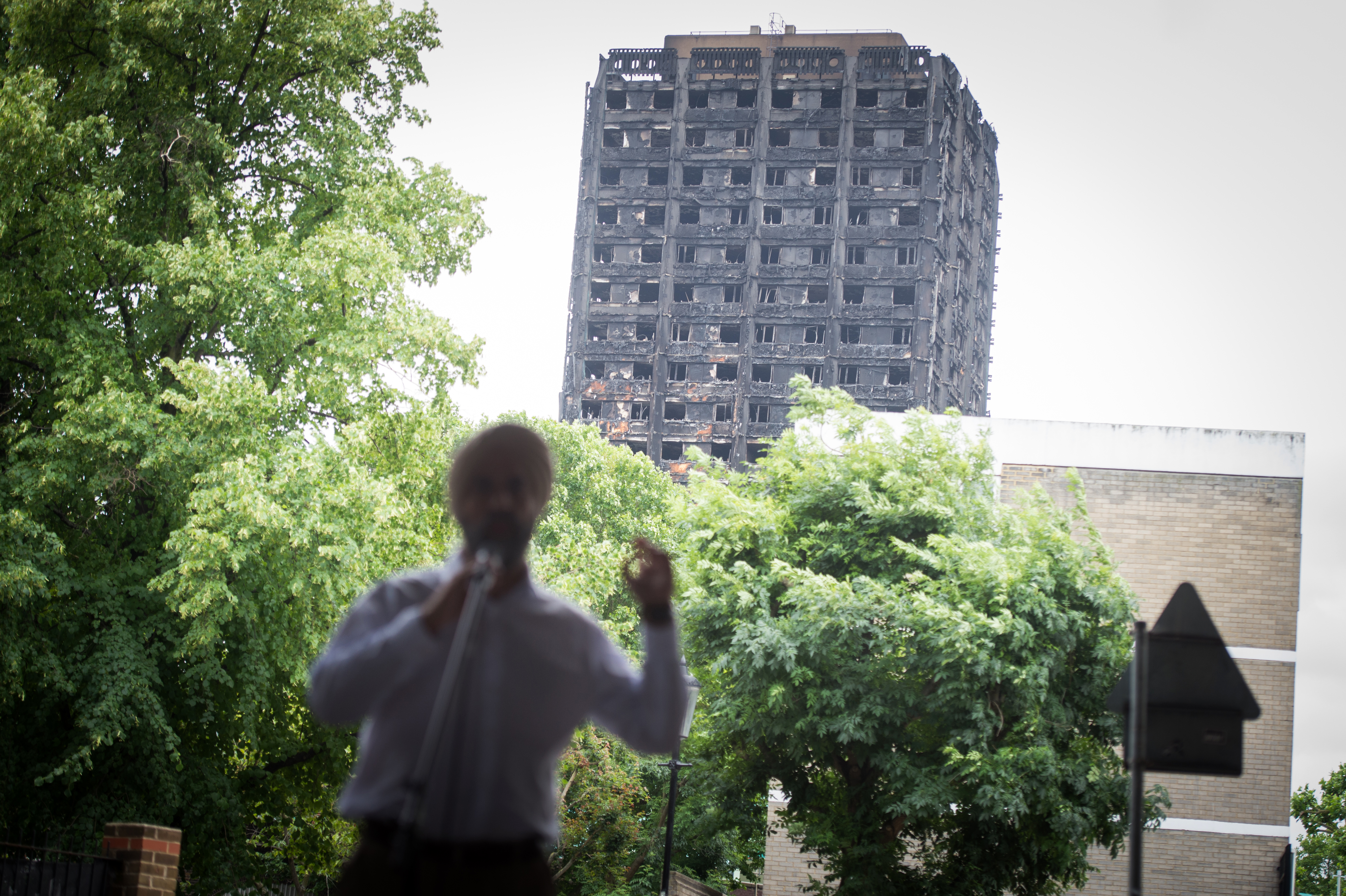 <p>A speaker in front of the burned Grenfell Tower. Flickr/Catholic Church England</p>