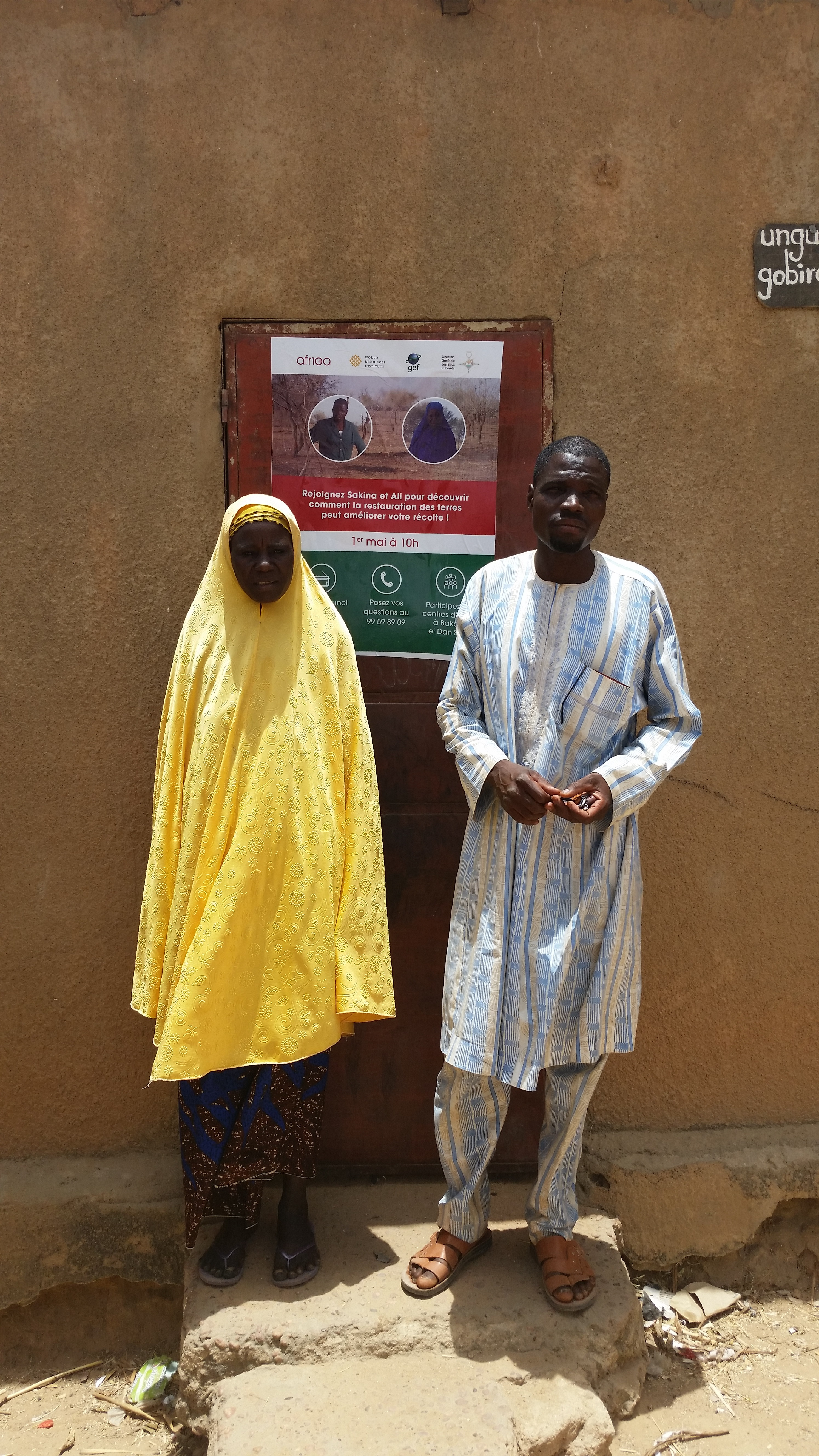 <p>Mati and Malam with the poster advertising their radio show. Photo: Salima Mahamoudou</p>