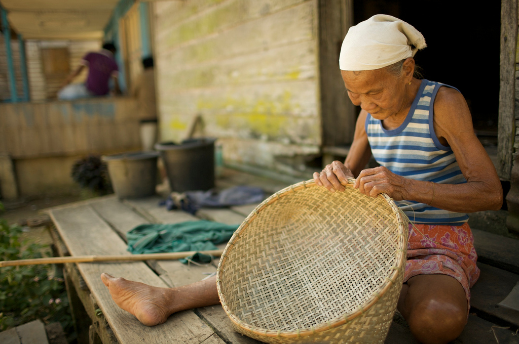 <p>A woman in Indonesia\'s Dayak community weaves a basket. Photo by Rainforest Action Network/Flickr</p>
