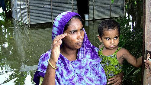 Mother and child at flooded home in Bangladesh.