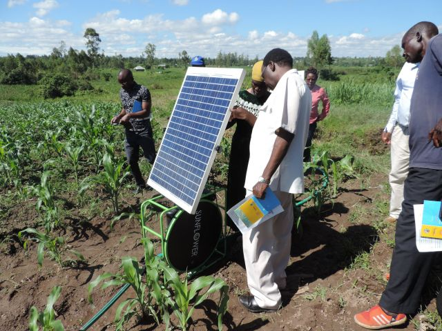 A farmer showcases her solar power in Kenya.