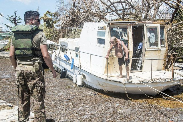 Houseboat stuck in low-lying water and debris on Scout Key