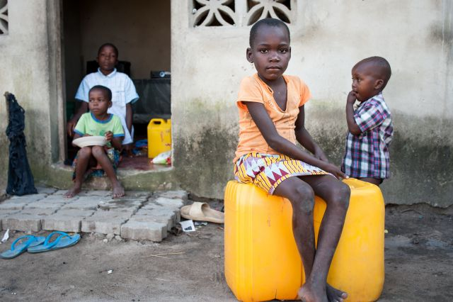 A child sits on water jugs provided after Cyclone Idai. Flickr/EU Civil Protection and Humanitarian Aid