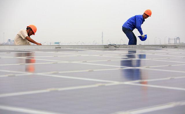 Installing solar panels on the Hongqiao Passenger Rail Terminal in Shanghai, China. Photo by Jiri Rezac/The Climate Group