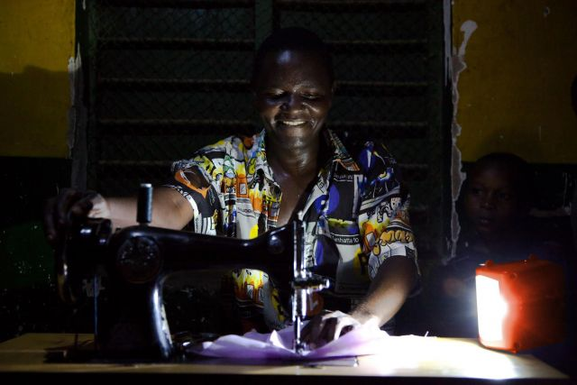 Electricity has far-reaching impacts on people's livelihoods. This Tanzanian tailor can sew at night thanks to solar power. Photo by Theo Steemers/USAID