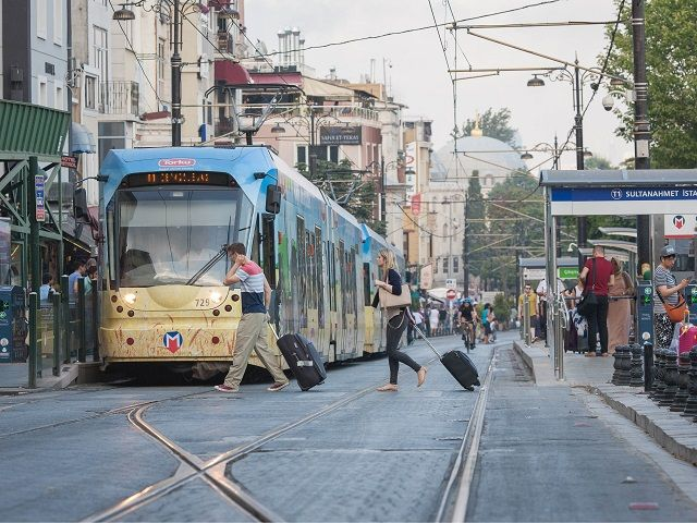 Two people crossing with luggage in front of tramway, Historic Peninsula, Istanbul, Turkey