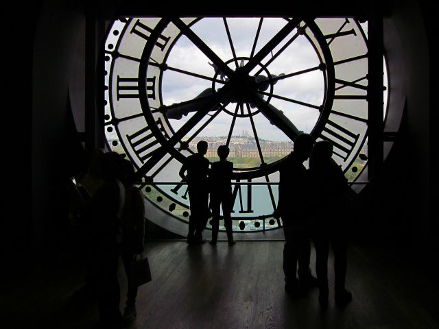 Visitors behind the clock at the Musée d'Orsay in Paris. Photo by Guy Dugas/Pixabay.