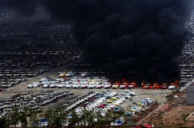 A black cloud of smoke rises from vehicles set on fire by the explosion in Tianjin. Photo by Karl-Ludwig Poggemann/Flickr
