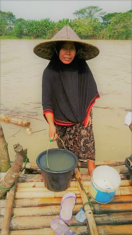 Woman drawing water from the Ciujung river