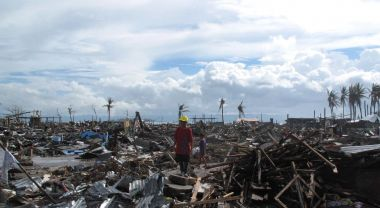 People stand amidst the devastation caused by typhoon Haiyan.