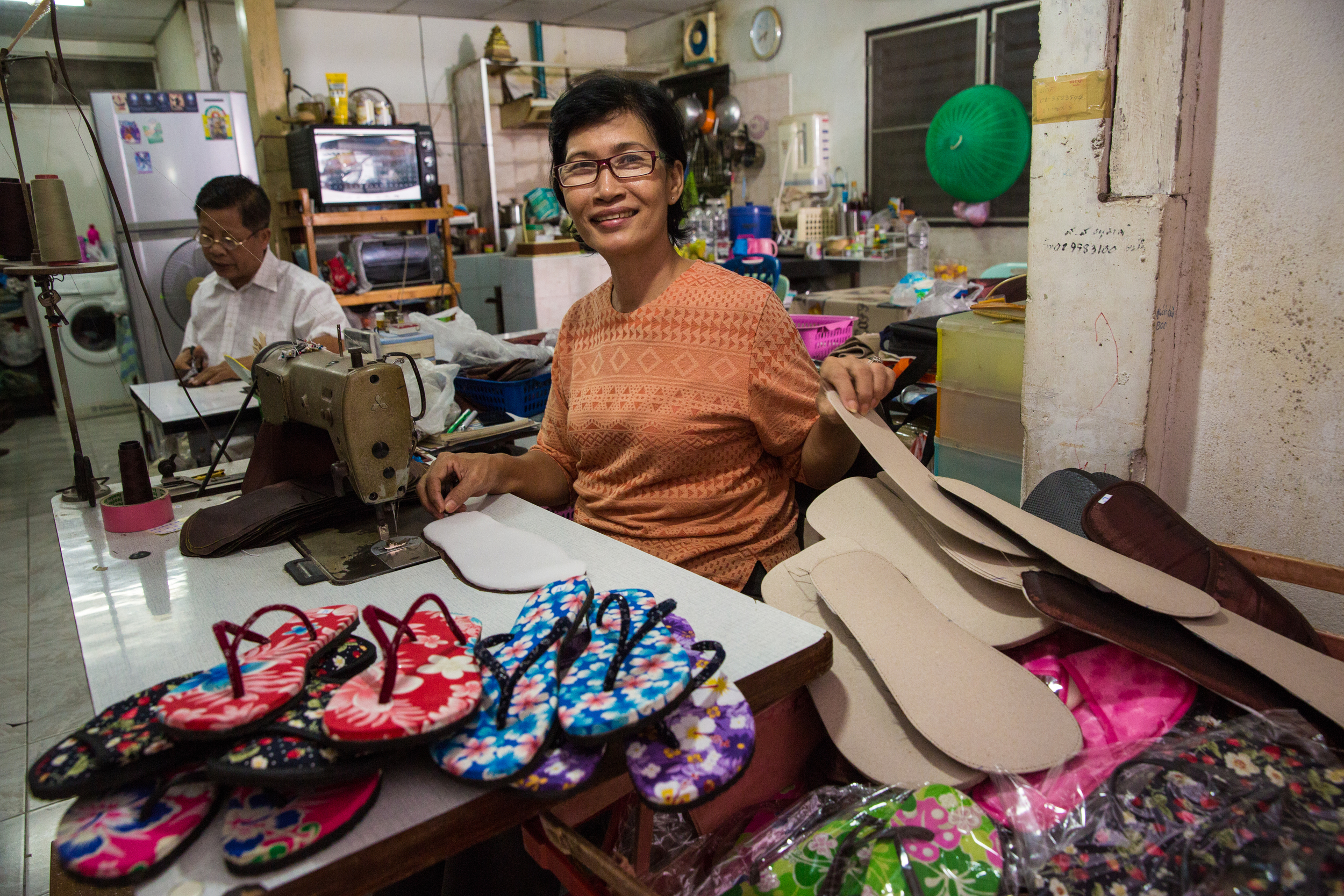 <p>Rattana Chalermchai works with her husband, Mongkol, at home. A former factory worker, Rattana was laid off during the economic crisis in 1997. She now supplies hand-made flip-flops to a resort. She and her husband are long-time members of HomeNet Thailand, and have contributed to several policy campaigns for informal workers, including the Universal Healthcare Coverage. Through HomeNet, they have also helped Thailand's home-based garment workers to officially register themselves as a garment cooperative. As legal entity, the cooperative has broadened opportunities to get work orders, and more importantly, strengthen a movement of home-based workers. (Photo by Paula Bronstein/Getty Images Reportage).</p>