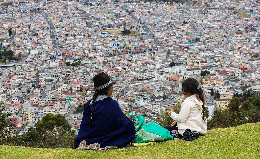 <p>An indigenous woman and girl look over Quito, where the government consulted with residents to include their traditional knowledge in climate adaptation solutions. Photo by Diego Delso/Wikimedia Commons.</p>
