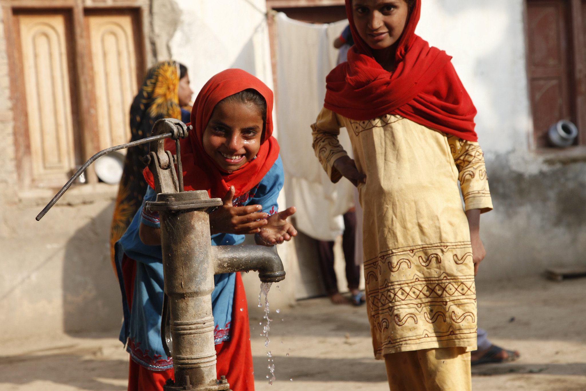 <p>Girls in Sindh, Pakistan, at their village water pump. Photo by Russell Watkins/DFID.</p>