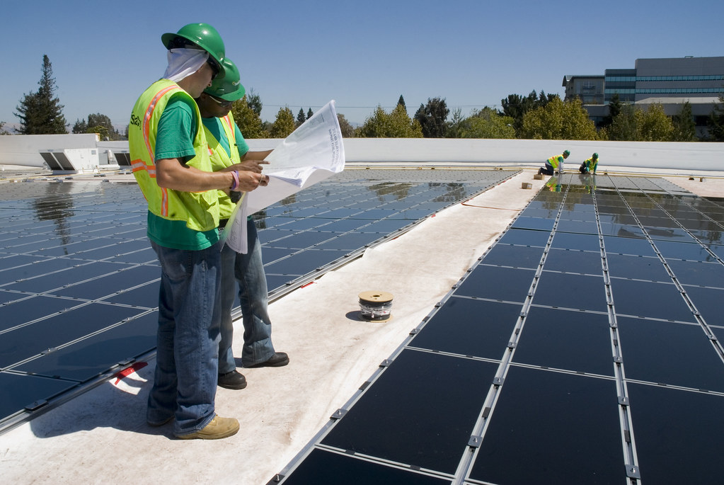 <p>Workers install solar panels on a Walmart store in California. Photo by Walmart/Flickr</p>