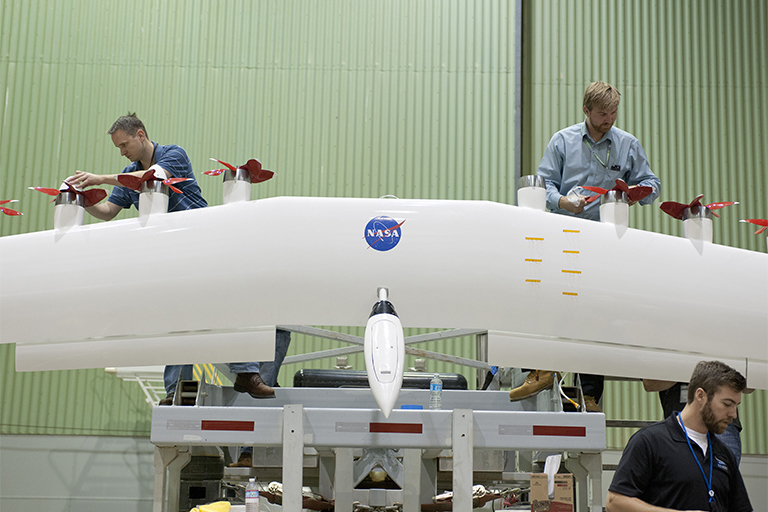 <p>NASA engineers work on the wing of a test electric airplane. Photo by Tom Tschida/NASA</p>