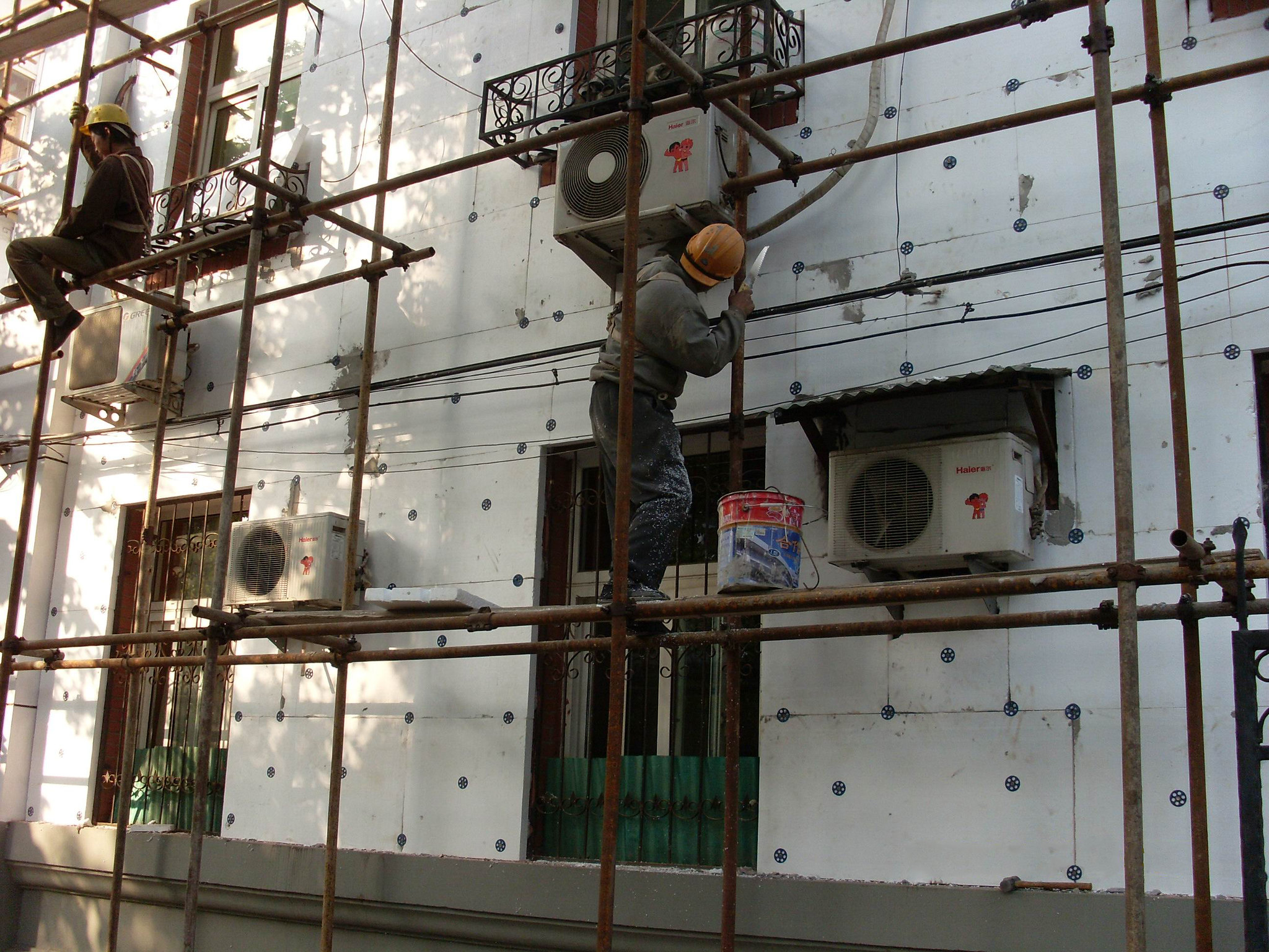 <p>Workers insulate a building in China. Good insulation, air quality and lighting cut buildings\' energy use, and they also improve occupants\' health. Photo by Pacific Northwest National Laboratory/Flickr</p>