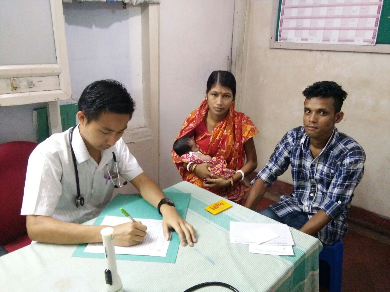 <p>A couple visits a pediatrician at EHA hospital in Alipur, India. Photo by EHA Hospital</p>