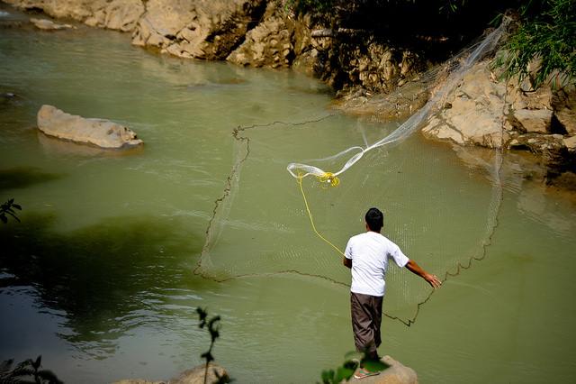 <p> Nelayan membentangkan jalanya di Yogyakarta. Perlindungan perikanan merupakan bagian penting dalam mewujudkan visi pembangunan rendah karbon Indonesia. Foto oleh Lembaga Penelitian Padi Internasional.</p>