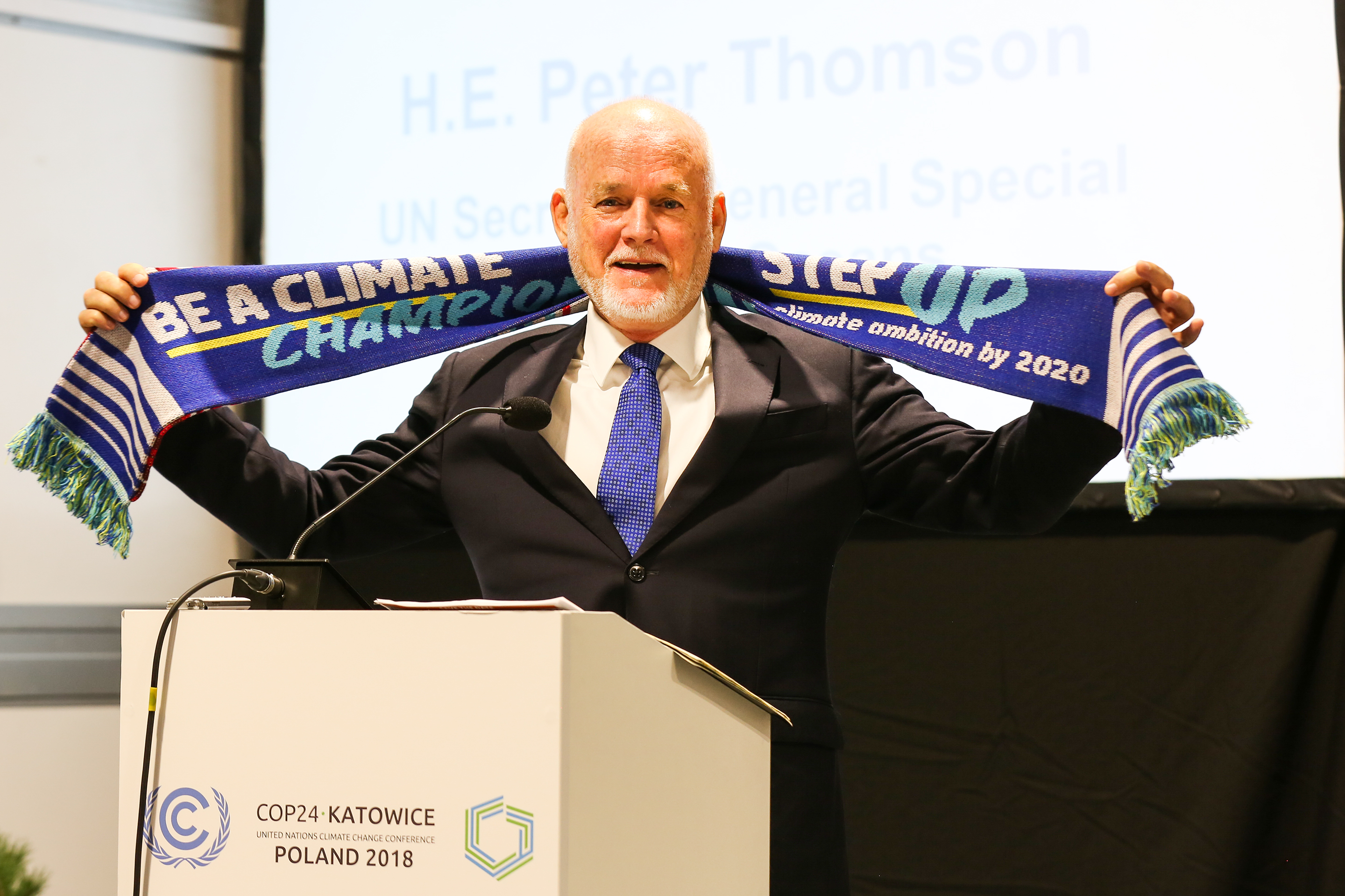 <p>Peter Thomson, UN Special Envoy for the Oceans, displays COP24 scarf urging countries to step up climate ambition by 2020. Photo by IISD</p>