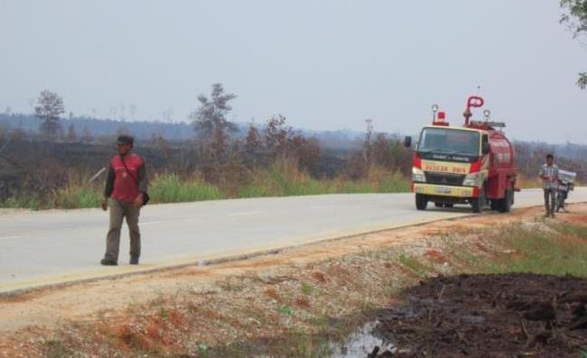 <p>Pekerja Wilmar dan tentara Indonesia melakukan patroli untuk mencari kebakaran dengan truk yang penuh dengan air. Foto oleh: Julius Lawalata, Maret 2014.</p>