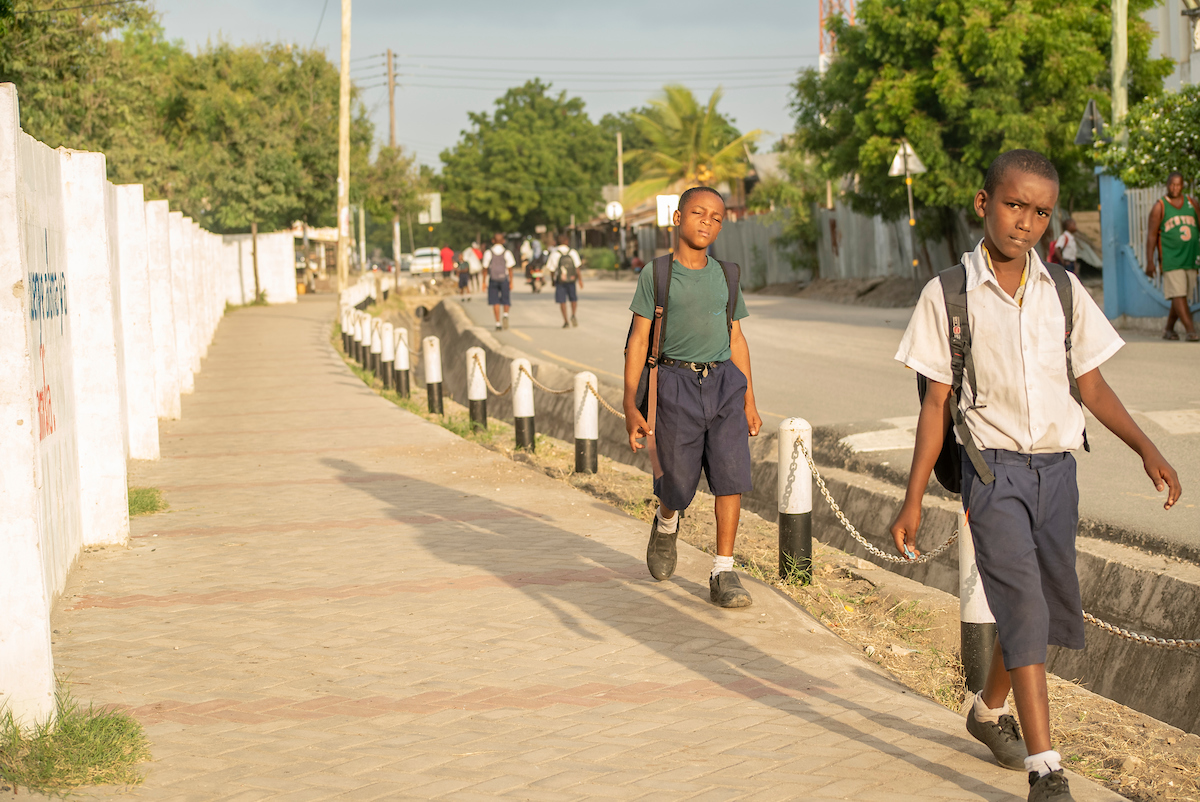 <p>Children in Dar es Salaam walk to school safely on a footpath created by the School Area Road Safety Assessments and Improvements (SARSAI) project, led by Ayikai Charlotte Poswayo. Photo by Kyle Laferriere</p>