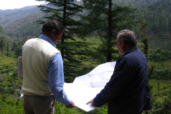 <p>SBA Hydro founder S.K. Sharma (right) reviews plans for a new 100KW micro hydro plant. Photo credit: Saurabh Lall</p>