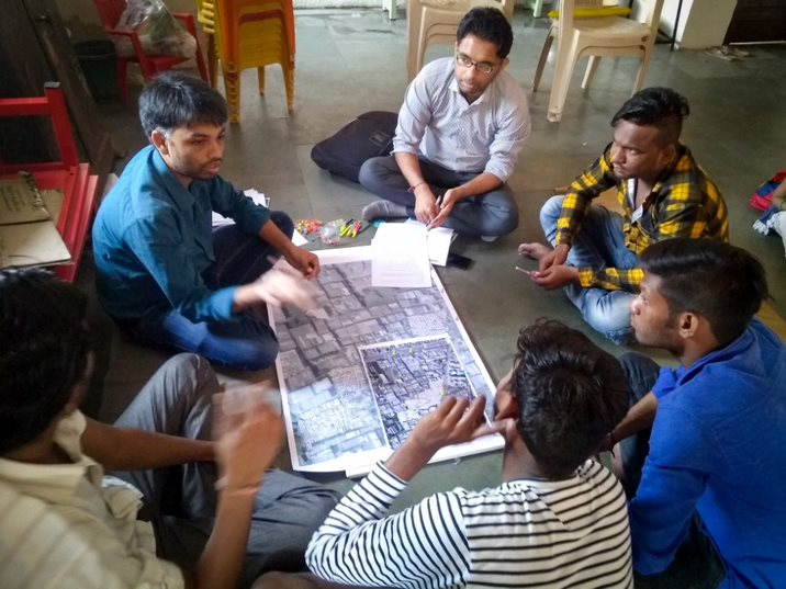 <p>Men from the Morarji Vasahat community mark on a map areas that are most prone to flooding and streets used for evacuations. Photo by Lubaina Rangwala/WRI</p>