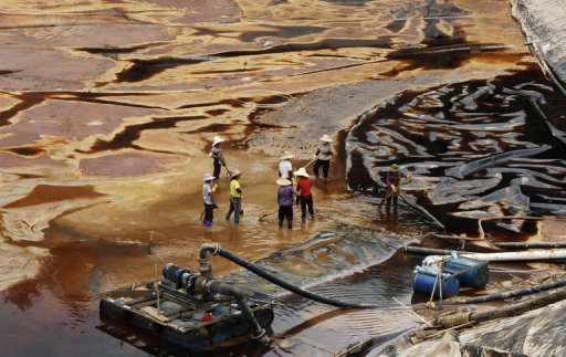 <p>Workers drain away polluted water from the Zijin copper mine. Photo credit: PhysOrg</p>